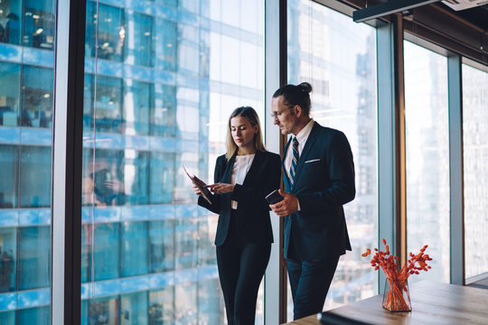 Mature caucasian male and female company workers dressed in elegant suits checking information on professional financial website using 4g wireless for browsing internet on digital touch pad