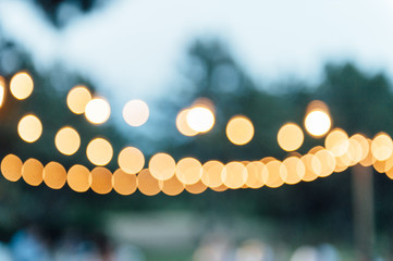Light bulb decor in outdoor party. blurred photo