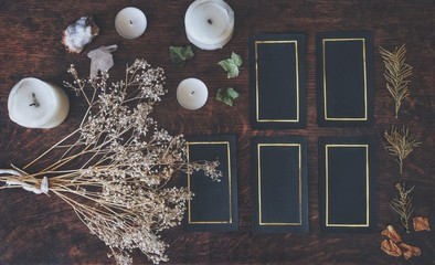 Tarot 5 card spread on a nature display (flat lay) . Hand made tarot cards on a dark wooden table surrounded with dried flowers, herbs and white candles. Black cards with golden shiny rectangular rim