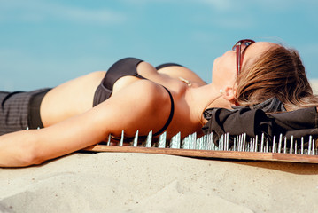 extreme yoga relaxation and self-development - beautiful office woman laying nacked back on the board with nails in desert outdoor