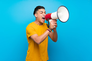Young man with yellow shirt over isolated blue background shouting through a megaphone