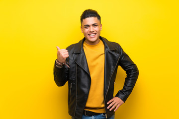Young man over isolated yellow background pointing to the side to present a product