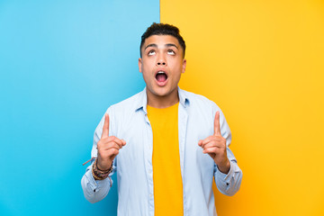 Young man over isolated colorful background pointing with the index finger a great idea
