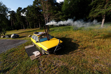 A smoke runs out of an old yellow Audi car converted into a small sauna in Tallinn