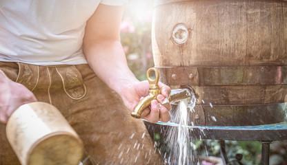 bayerischer Mann in Lederhose sticht ein Holzfass Bier im Garten an und genießt den ersten Schluck Wall mural