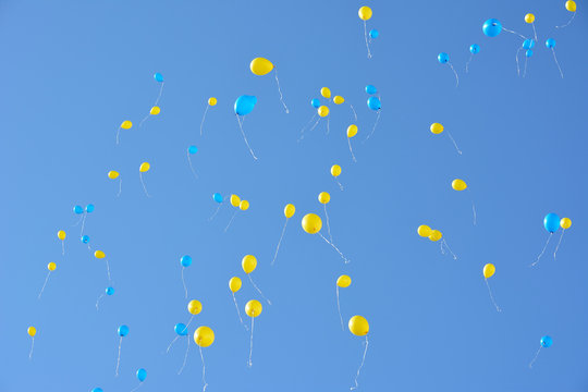 Many blue and yellow balloons flying high in the sky. Blue sky with lots balloons.