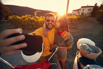 Man and woman on romantic journey on scooter at sunset and take selfie..