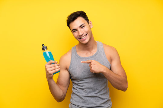 Handsome sport man over isolated background with a bottle of soda