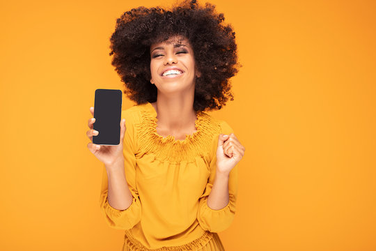 Excited afro girl with mobile phone.