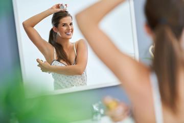 Beautiful brunette woman using deodorant in the bathroom