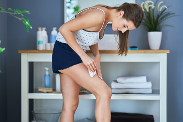 Beautiful brunette woman shaving legs in the bathroom
