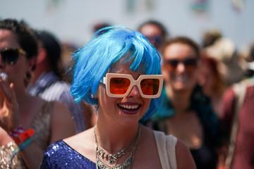 A festival goer wears a blue wig at Glastonbury Festival in Somerset