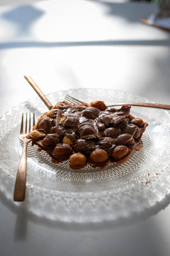 Bubble waffle with chocolate on a transparent plate with an antique design with golden fork and knife on white wooden table