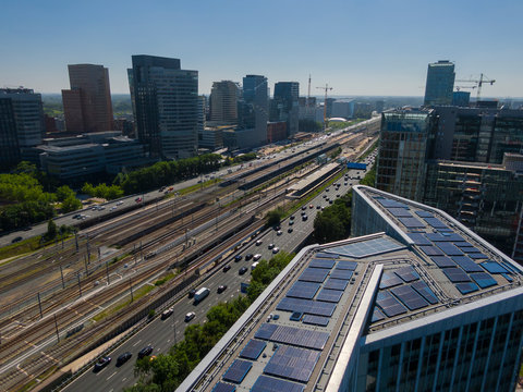 Aerial of modern sustainable office building with solar panels, part of transit oriented development next to train station in Amsterdam Zuidas business district