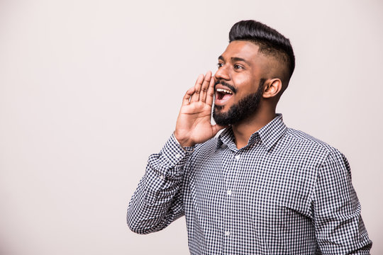 An angry indian man pulling his hair and screaming, isolated on a white background.