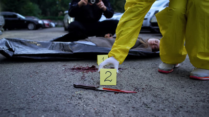 Police making photo and fixing numbers of evidence, dead body and knife on road