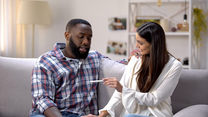 Woman showing pregnancy test to happy Afro-American boyfriend, positive result
