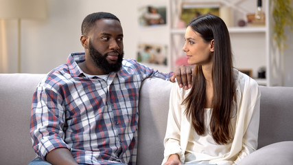 Afro-american boyfriend suspiciously looking at girlfriend, surprise for beloved