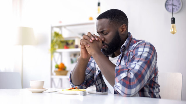 African-American man praying before lunch, thanking God for meal, religion