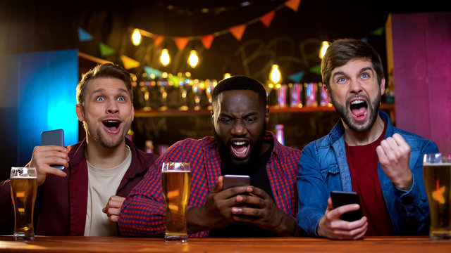 Excited friends rejoicing watching horse race and making bets online, income