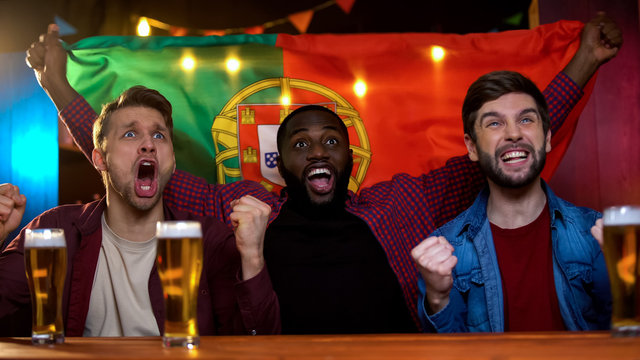 Cheerful portuguese multiracial men celebrating soccer team victory, waving flag
