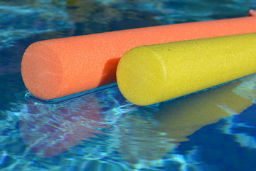 Pool noodles floating on water, close up