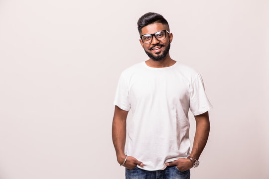 Young indian handsome man in eyesglasses standing isolated on white background