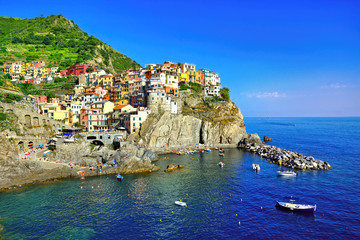 Fototapete - Beautiful Cinque Terre village of Manarola, Italy. Colorful cliff side village along the sea with boats.