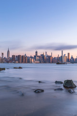 Midtown manhattan view from east river with rocks on foreground at sunrise  long exposure photo