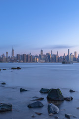Midtown manhattan view from east river with rocks on foreground at blue hour  long exposure photo