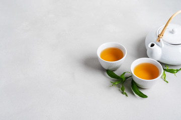 Photo sur Plexiglas The Tea concept with white tea set of cups and teapot surrounded with fresh tea leaves on concrete background with copy space.