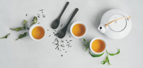 Tea concept with three white cups of tea and teapot surrounded with fresh green tea leaves and dry leaves,  top view composition on concrete background with copy space. Long banner. Wall mural