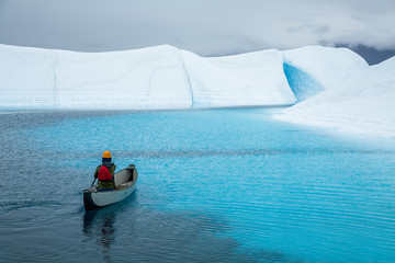 Wall Mural - Dark rainy day paddling a canoe on a blue pool deep in the wilderness on an Alaskan glacier.