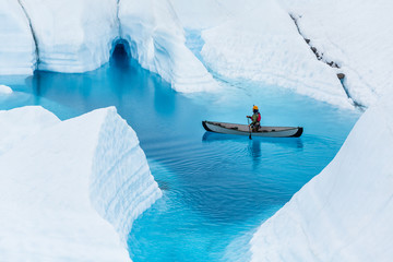 Glacier kayaking over ice cave and deep blue lake in the rain. Wall mural