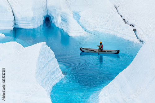 Wall mural Glacier kayaking over ice cave and deep blue lake in the rain.