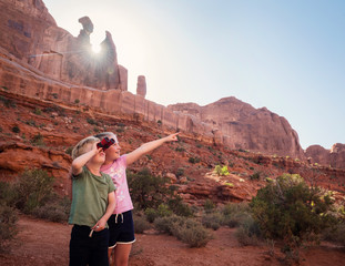 Children sightseeing holding binoculars and pointing at rock formations in Moab, Utah