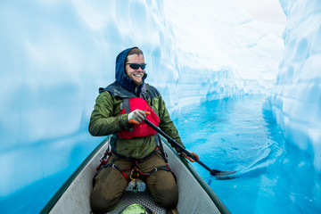 Wall Mural - Ice climber paddling through narrow canyon cut through glacier ice, filled with deep blue water.