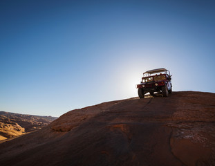 Group of people riding in off-road vehicle on desert trail in Moab, Utah