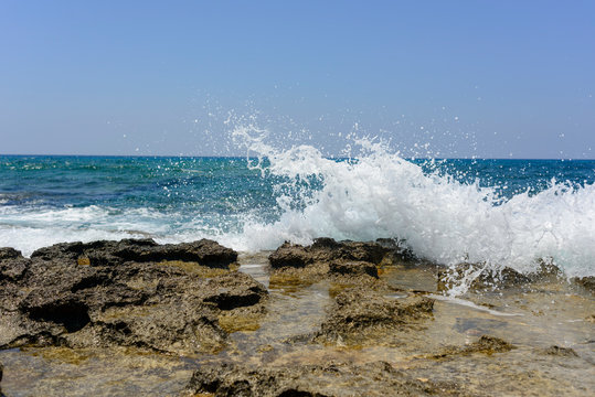 splashing waves crashing against a stone beach