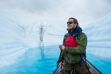 Wall Mural - Happy man excited to paddle a canoe on a supraglacial lake on the Matanuska Glacier