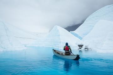 Wall Mural - Ice climber in inflatable canoe paddling across a glacier lake on top of the Matanuska Glacier in Alaska.