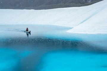 Wall Mural - Paddling a canoe across a blue glacier lake in the rain. Matanuska Glacier deep blue pool (supraglacial lake).