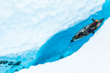 Wall Mural - Ice climber canoeing in narrow ice canyon from above.