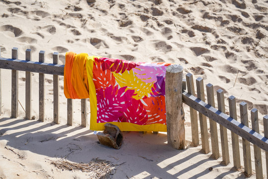 bright yellow pink red and orange colorful beach towel drying over a weathered wooden  storm fence