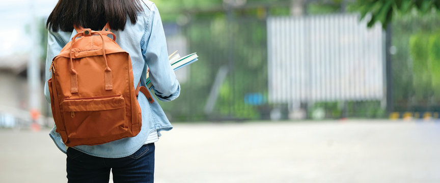 Back of student girl holding books and carry school bag while walking in school campus background, copy space banner, education, back to school concept