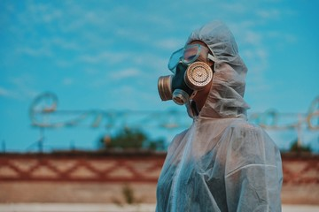 The scientist put on a respirator and a white protective suit against radiation. Close-up profile of a girl who cares about ecology. Wall mural