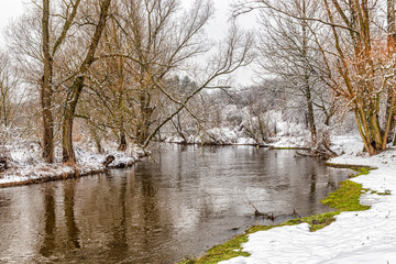 Winter landscape in the snowy forest and Warta river in Mstow, Poland