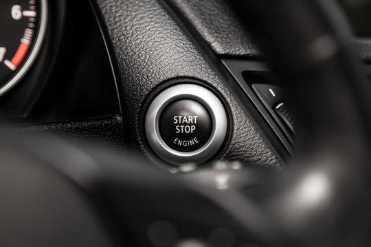 Car engine push start stop button ignition remote starter. Car dashboard:  black engine start stop button, car interior details. Soft focus