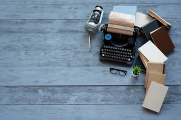 Old typewriter on a writer wooden desk flat lay background with copy space.