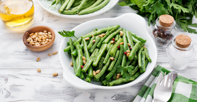 Sauteed green beans with pine nuts in a baking dish, healthy side dish.